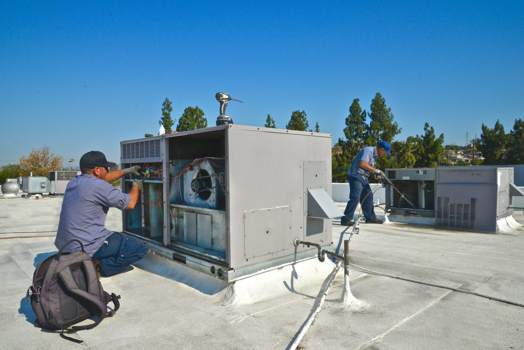 2 ACS employees on a roof working on a cooling system
